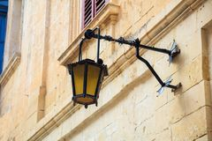 Malta, Mdina. Old lantern lamp in the medieval city with the narrow streets and houses limestone facades. Mdina, Malta island. Old lantern lamp in the medieval Stock Photography