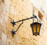 Malta, Mdina. Old lantern lamp in the medieval city with the narrow streets and houses limestone facades. Mdina, Malta island. Old lantern lamp in the medieval Stock Photos