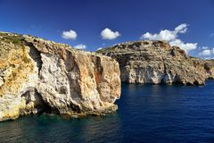 Malta Mediterranean seacoast. Limestone rocks with caves and clear water near popular tourist attraction Blue Grotto on a sunny day Stock Photography
