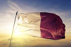 Malta national flag textile cloth fabric waving on the top. Maltese national flag textile cloth fabric waving on the top sunrise mist fog Royalty Free Stock Photos