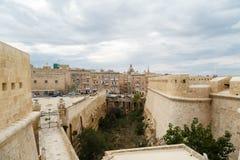 Malta National War Museum. VALLETTA, MALTA - OCTOBER 30, 2015 : View of National War Museum in Valletta, Malta with high yellow stone walls, on cloudy sky Stock Image
