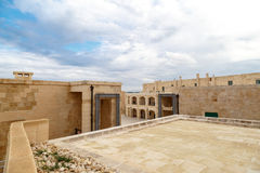 Malta National War Museum. View of National War Museum in Valletta, Malta with high yellow stone walls, on cloudy sky background Royalty Free Stock Photo