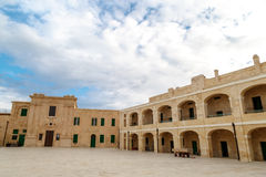 Malta National War Museum. View of National War Museum in Valletta, Malta with high yellow stone walls, on cloudy sky background Stock Photos
