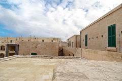 Malta National War Museum. View of National War Museum in Valletta, Malta with high yellow stone walls, on cloudy sky background Royalty Free Stock Images