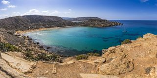 Malta - Panoramic view of Ghajn Tuffieha sandy beach with sail b. Oat, blue sky and crystal clear green sea water Royalty Free Stock Image