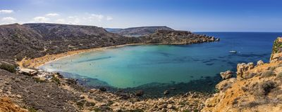 Malta - Panoramic view of Ghajn Tuffieha sandy beach with sail boat. Blue sky and crystal clear green sea water Royalty Free Stock Photos