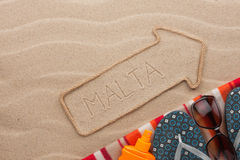 Malta pointer and beach accessories lying on the sand. As background Royalty Free Stock Image