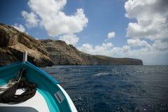 Malta, rotsachtige overzeese kust van een kleine boot op overzees Stock Afbeelding