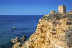 Malta - Sail boat at Ghajn Tuffieha tower on a hot summer day. With crystal clear blue sea water Stock Images
