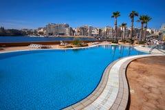 Malta-Saint Julien Bay View- 16 April 2016. Pool View on Saint Julien , Malta with palm trees Stock Photo