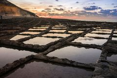 Roman salt rock pools in Malta. Malta Salt rock pools are amazing. Still used and perfect for reflections. They sweep the salt out once it dries in summer Stock Photos