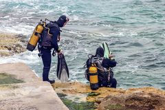 Malta Scuba divers enter the sea. Scuba Divers enter the Mediterranean off the coast of Malta at St. Elmos` Bay from the rocky coast Stock Images