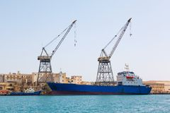 Malta Shipyards. Ship and Port cargo crane in Shipyards harbor of Malta in clear weather on a background of blue sky Royalty Free Stock Photography