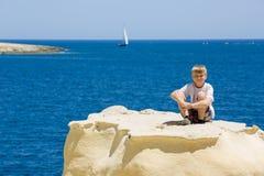 Young blonde kid smiles on coastal rock, blue sea background Royalty Free Stock Photos