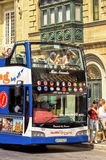 Malta - Streets of Mosta. Hop on hop off double decker bus with holiday-makers during sightseeing trip across the island - Mosta, Malta Stock Image
