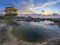 Malta - Sunrise at St.Peter`s Pool with huge rocks of Delimara. And reflections of the sky and clouds Stock Photo
