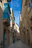 Malta, Three Cities, Narrow Middle Ages street in L-Isla, Valletta. Scenic, narrow Medieval street and buildings in L-Isla, one of the Three Cities, located stock photos