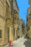 Malta - Three Cities. Narrow street and buildings in the oldest part of the historic Città Vittoriosa, main city of Malta from 1530 to 1571 - Vittoriosa or Royalty Free Stock Photo