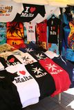 Malta Tourism. Souvenir T-Shirts from the Mediterranean island of Malta. For sale at a local market in the fishing village of Marsa Slok Stock Image