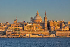 Malta - Valetta - Valetta`s cityscape at dusk with harbor waterf. Valetta`s cityscape at dusk with harbor waterfront and our lady of mount carmel madonna tal Stock Photo