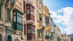 Malta, Valletta, building facade with covered balconies, with blue sky background, perspective view. Malta, Valletta, traditional house building facade with Royalty Free Stock Image