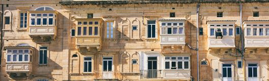 Malta, Valletta, building facade with covered balconies, front view, banner. Malta, Valletta, traditional house building facade with sandstones and covered Stock Images