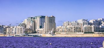 Malta Valletta. Modern Sliema multi-storey buildings, blue sea and sky background. Malta Valletta. Modern Sliema waterfront buildings, blue sea and sky Royalty Free Stock Image