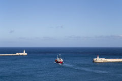 Malta Valletta lighthouses and open blue ocean with red ship Stock Photos