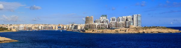 Malta, Valletta. Sliema town with multistorey buildings, blue sea and blue sky with few clouds background. Panoramic view, banner. Malta, Valletta. Sliema town Stock Photo