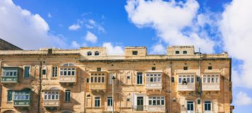 Malta, Valletta, building facade with covered balconies, with blue sky background, front view. Malta, Valletta, traditional house building facade with sandstones Stock Photos