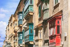 Malta, Valletta, building facade with covered balconies, with blue sky background, perspective view. Malta, Valletta, traditional house building facade with Stock Image