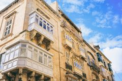 Malta, Valletta, building facade with covered balconies, with blue sky background, perspective view. Malta, Valletta, traditional house building facade with Stock Photo