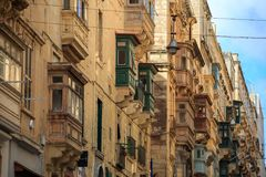 Malta, Valletta, traditional sandstone buildings with colorful wooden windows on balconies. Blue sky with clouds background. Close. Malta, Valletta, traditional Stock Images