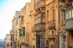 Malta, Valletta, traditional sandstone buildings with colorful wooden windows on balconies. Blue sky with clouds and sea backgroun. Malta, Valletta, traditional Stock Image