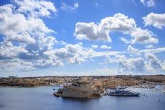 Malta, Valletta Uroczysty schronienie w śródziemnomorskim Błękitny niebieskie niebo z few i morze chmurniejemy tło komunalne jede Zdjęcie Stock
