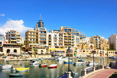 Malta. View of modern buildings and fishing boats in sea bay. Malta Stock Photography