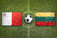 Malta vs. Lithuania flags on soccer field Royalty Free Stock Photos