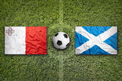 Malta vs. Scotland flags on soccer field. Malta vs. Scotland flags on a green soccer field Royalty Free Stock Image