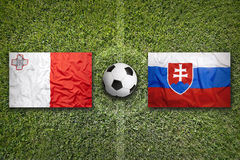 Malta vs. Slovakia flags on soccer field. Malta vs. Slovakia flags on green soccer field Royalty Free Stock Images