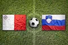 Malta vs. Slovenia flags on soccer field. Malta vs. Slovenia flags on green soccer field Royalty Free Stock Photo