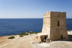 Malta watchtower and blue ocean. One of the many watchtowers from the era of the maltese knight order along the coastline of Malta Stock Photo