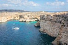Maltan kustlinje med höga klippor och en segelbåt arkivfoto