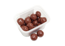 Malted milk balls covered chocolate in small plastic container. Malted milk balls covered milk chocolate in the small transparent plastic container and two Stock Photography