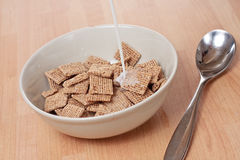 Malted squares. A bowl of dry malted cereal with milk being poured on top Royalty Free Stock Image