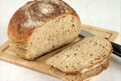Malted wholemeal loaf. Sliced on a bread board Royalty Free Stock Photos