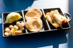 Maltese appetizer platter in restaurant. Traditional maltese appetizer platter set of eggplant pate,white beans, salty crackers and toasted bread with garlic and Royalty Free Stock Image