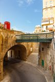 Maltese architecture in Valletta, Malta. Traditional narrow street, old houses, arch, tunnel and footbridge in Malta. Maltese architecture in Valletta, Malta Royalty Free Stock Photos