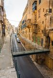 Maltese architecture in Valletta, Malta. Traditional narrow street, old houses and footbridge in Malta. Maltese architecture in Valletta, Malta Stock Photo