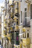 Maltese balconies in Valletta. Typical narrow street on the island of Malta. Buildings with traditional colorful maltese balconies in historical part of Stock Images
