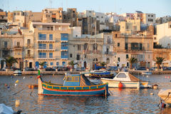 Maltese boat Luzzu moored in the creek with Kalkara city on th. KALKARA, MALTA - JULY 23, 2015: The view of Kalkara city over the  bay with moored traditional Royalty Free Stock Images
